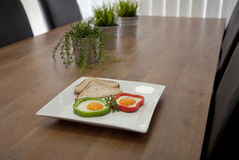 Fried Eggs. In capsicum/peppers rings on a white plate Royalty Free Stock Photos