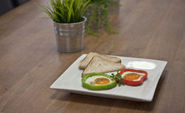 Fried Eggs. In capsicum/peppers rings on a white plate Royalty Free Stock Image