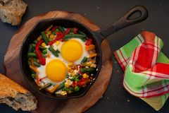Fried eggs in a cast iron. Pan with peppers, tomatoes, beans and bread Royalty Free Stock Photography