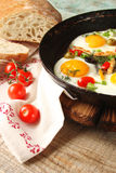 Fried eggs in a cast iron pan with peppers, tomatoes, capers, he Royalty Free Stock Photo