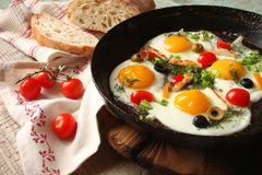 Fried eggs in a cast iron pan with peppers, tomatoes, capers, he Royalty Free Stock Photography