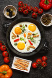 Fried eggs in a cast iron pan with peppers, tomatoes, capers, he Royalty Free Stock Images
