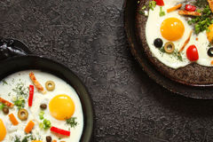 Fried eggs in a cast iron pan with peppers, tomatoes, capers, he Stock Photography