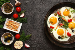 Fried eggs in a cast iron pan with peppers, tomatoes, capers, he Royalty Free Stock Image