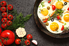 Fried eggs in a cast iron pan with peppers, tomatoes, capers, he Royalty Free Stock Photos