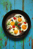 Fried eggs in a cast iron pan with peppers, tomatoes, capers, he Stock Photos