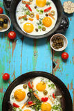 Fried eggs in a cast iron pan with peppers, tomatoes, capers, he Stock Photo
