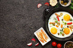 Fried eggs in a cast iron pan with peppers, tomatoes, capers, he Stock Images