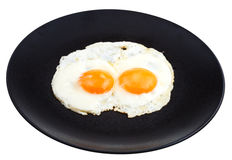Fried eggs on ceramic black plate Royalty Free Stock Photos