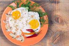 Fried eggs with champignons, dill and red chili pepper Stock Images
