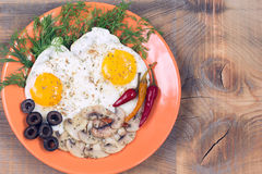Fried eggs with champignons, olives, dill and red chili pepper Royalty Free Stock Images