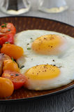 Fried eggs and cherry tomatoes Stock Images