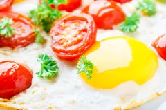 Fried eggs with cherry tomatoes Royalty Free Stock Photography