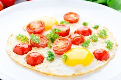 Fried eggs with cherry tomatoes Stock Photos