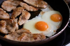 Fried eggs and chicken meat on pan Stock Photos