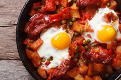 Fried eggs with chorizo in the pan close up. horizontal top view Stock Photo