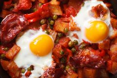 Fried eggs with chorizo, potatoes, peas and tomato close up Royalty Free Stock Photos