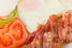 Fried eggs coloseup with bacon and vegetables Royalty Free Stock Image