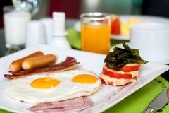 Fried Eggs con il formaggio della salsiccia, del bacon, del prosciutto e del pomodoro Fotografia Stock
