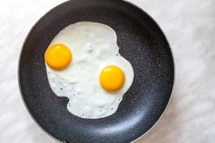 Fried eggs cooked in frying pan for breakfast, top view. Two fried eggs cooked in frying pan for early breakfast, top view stock photos