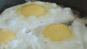 The fried eggs cooked on a pan close up slowmotion. The fried eggs cooked on a pan close up stock video