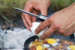 Fried eggs cooking on camp fire Royalty Free Stock Photography