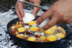 Fried eggs cooking on camp fire in smoke Stock Photography
