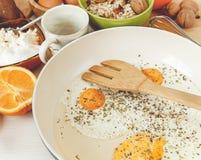 Fried Eggs dans la poêle, ingrédients de petit déjeuner Orange, pain, accessoires de cuisine Cuisson de la nourriture de matin Ta Photo libre de droits