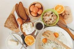 Fried Eggs dans la poêle, ingrédients de petit déjeuner Orange, pain, beurre, Porrige, haricots Coffe Accessoires de cuisine Cuis Photographie stock