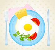 Fried eggs on a dish are decorated a tomato and ch Royalty Free Stock Photography
