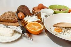 Fried Eggs en el sartén, ingredientes del desayuno Naranja, pan, mantequilla Accesorios de la cocina Cocinar la comida de la maña Imágenes de archivo libres de regalías