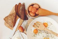 Fried Eggs en el sartén, ingredientes del desayuno Pan, mantequilla Accesorios de la cocina Cocinar la comida de la mañana Vector Imagen de archivo