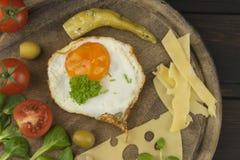 Fried Eggs en un fondo de madera Huevos fritos y verduras en la tabla de cortar Imagen de archivo libre de regalías