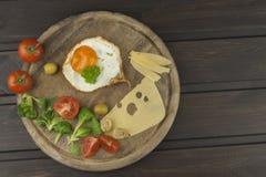 Fried Eggs en un fondo de madera Huevos fritos y verduras en la tabla de cortar Imagenes de archivo