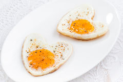 Fried eggs in the form of heart on white plate Royalty Free Stock Photo