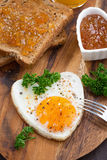 Fried eggs in the form of heart on wooden board, vertical Royalty Free Stock Photos