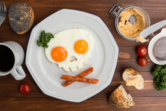 Fried eggs in the form of a skull on wooden table. stock photo