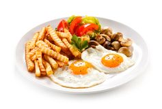 Fried eggs, French fries and vegetables. On white background royalty free stock photo
