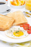 Fried eggs, fresh tomatoes and crunchy toast for breakfast Royalty Free Stock Photo