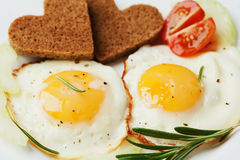 Fried eggs with fresh vegetables and toast in shape of heart on white plate. Delicious Breakfast royalty free stock photos
