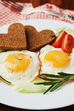 Fried eggs with fresh vegetables and toast in shape of heart on white plate Stock Images