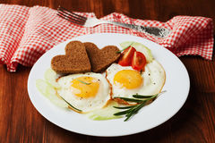 Fried eggs with fresh vegetables and toast in shape of heart on white plate Royalty Free Stock Image