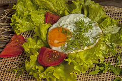 Fried eggs on fried eggs on the leaves of lettuce on a board Royalty Free Stock Image