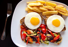 Fried eggs, fried potatoes and vegetables Royalty Free Stock Image