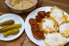 Fried eggs, fried sausage. With olive oil and pickled gherkins Stock Photography