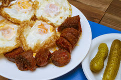 Fried eggs, fried sausage. With olive oil and pickled gherkins Royalty Free Stock Photo