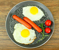 Fried eggs with fried sausages. Stock Photography