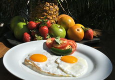Fried eggs fruit exotic breakfast. Two fried eggs on a white plate with garnish of tomato slices and a green chili pepper.fruit plate in the background stock photo