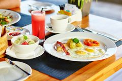 Fried eggs, fruit salad and juice for breakfast Royalty Free Stock Image