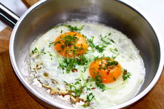 Fried eggs in a frying pan. Two fried eggs bruzzeln without any hurry in a metal frying pan. Cress as a decoration on top Stock Photo